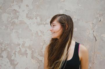 Teen Girl Profile Smiling Against Urban Wall
