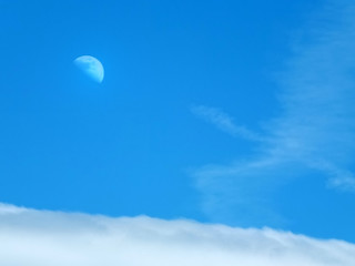 moon and clouds in a blue summer daytime sky