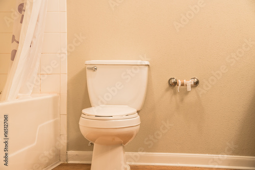 Close Up Of White Flush Toilet Bowl With Shower Curtain Tub And Empty Roll