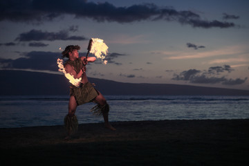 Traditional Hawaiian Fire Dancer twirling and tossing his flaming torch.