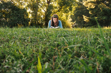 Teen girl reading book outside in field