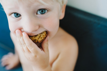 Toddler boy eating muffin at kitchen table in his diaper