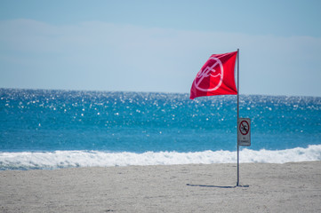 """red """"no swimming"""" flag flying on a Florida beach"""