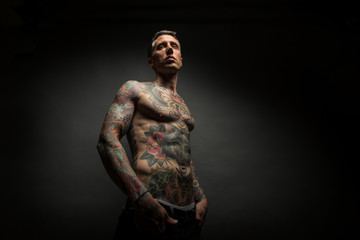 Middle aged tattooed man in the studio
