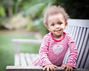 Portrait of toddler sitting on a bench smiling sweetly