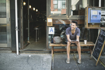 Hip Young Man Using Tablet Device Sitting Outside a Cafe