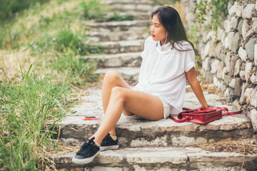 Young Asian Woman Listening to Music Outdoors