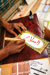 Mans hands writing in arabic caligraphy