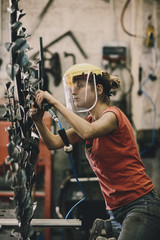 Young working woman using pneumatic file