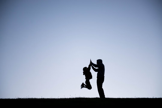 Evening silhouette of a boy jumping up to give his dad a high five