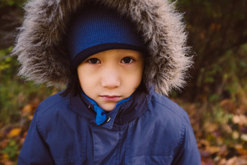 Closeup of serious child's face in fur lined hood