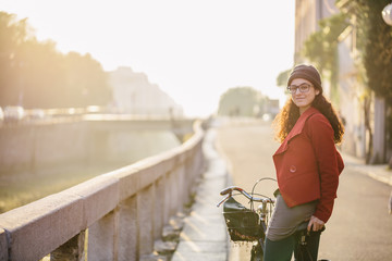 Young woman with a bicycle along canals of Milan