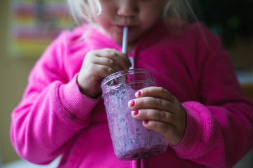Young girl sips blueberry smoothie with a straw.
