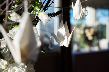 White origami paper cranes hang from twigs in a floral centerpiece