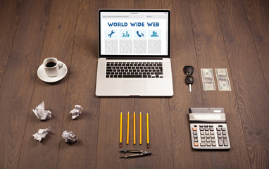 Laptop on wooden desk with office suplies