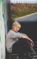 A teenage boy with his skateboard in  heavily graffitied location