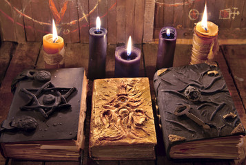 Mystic Halloween still life. Three magic books with burning candles on planks.