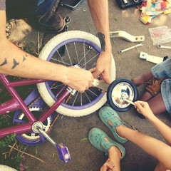 father putting training wheels on bike with children