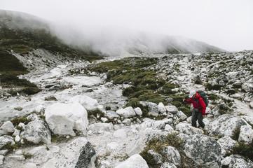 Female trekker walking up a track, Everest Region, Sagarmatha National Park, Nepal.