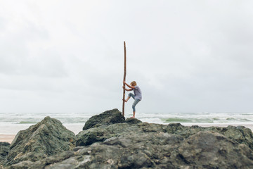 Wild marooned man standing on rocks holding a piece of driftwood