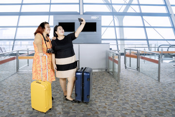 Fat women taking a photo in the airport