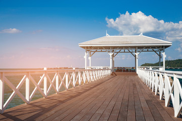 Wooden walking path leading to seacoast skyline with blue sky background