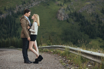 A couple standing on a gravel mountain road looking into each others eyes