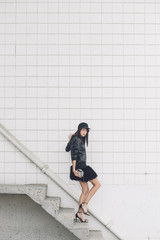 A woman walking down a flight of stairs dressed in all black
