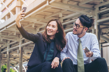 Business man and business woman enjoy using smartphone