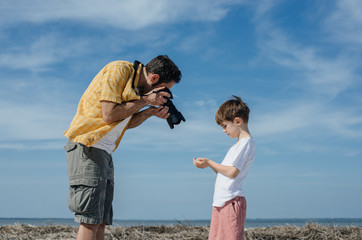 Father taking photo of his son at the beach