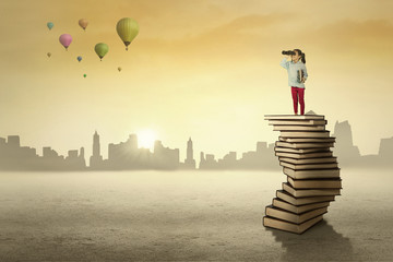 Schoolgirl standing on a pile of books