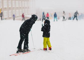 father teaches child to ski
