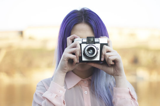 Young girl taking a photo with a retro camera