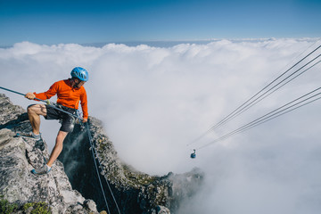 Mountaineer abseiling off the edge of Table Mountain, cable car in the distance