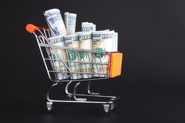 Shopping cart filled with one hundred dollar bills on a dark background.