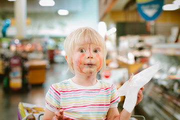 messy girl in shopping cart at deli counter