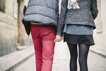 Young couple walking hand in hand in the city