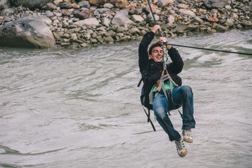 Young man on a canopy or zipline crossing a river on adventure travel