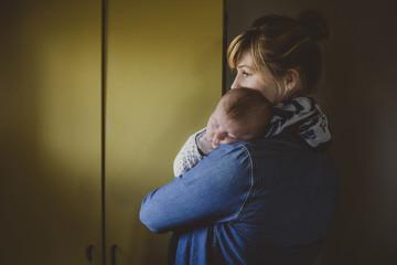 Young mom cuddling sleeping baby girl
