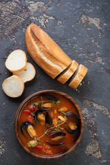 Wooden bowl with mussels soup and sliced baguette, above view over brown stone surface, vertical shot