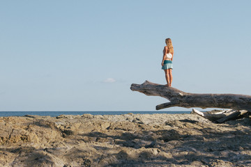 Girl looking out over the ocean on a drift wooden trunk