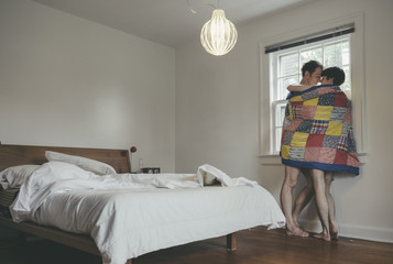 Embracing Gay Men Couple with Blanket Looking Out their Bedroom Window