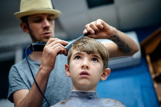 Young boy gets a haircut at a barber shop