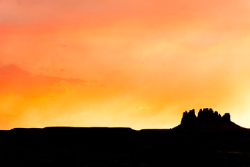 single mesa or rock formation in silhouette against a beautiful red and orange evening sky