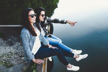 Pretty brunette girls sitting on the pier near lake