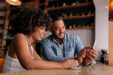 Smiling couple at cafe using mobile phone