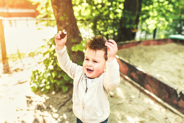 Pretty little boy playing outdoor on the playground