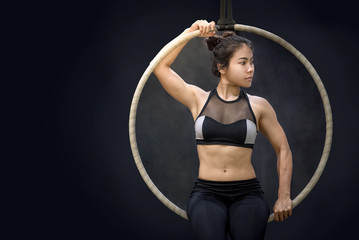 young asian acrobatic woman posturing on aerial hoop or aerial ring, gymnastics exercise on black background