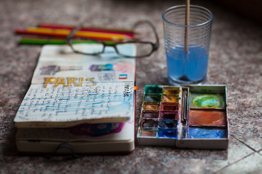Journal open to a page about Paris with paint and pencils
