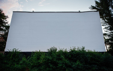 Blank screen at dusk at a drive-in movie theater